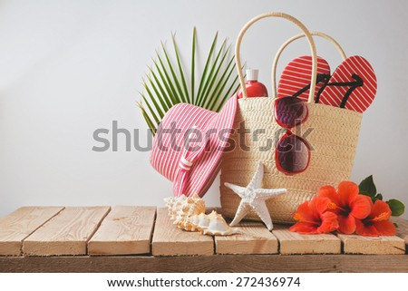 Summer beach bag and hibiscus flowers on wooden table. Summer holiday vacation concept. View from above - stock photo