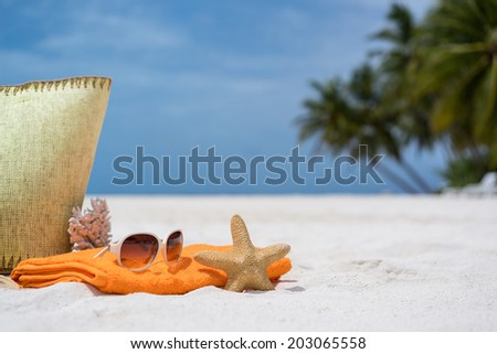 Summer beach bag with coral,towel, sunglasses and coral on sandy beach - stock photo