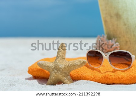 Summer beach bag with towel, sunglasses and coral on sandy beach - stock photo