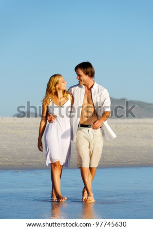 summer beach couple embracing and walking along the sand. - stock photo