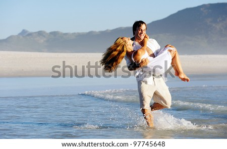 Summer beach couple spinning and embracing in the water, laughing and splashing together having fun. - stock photo
