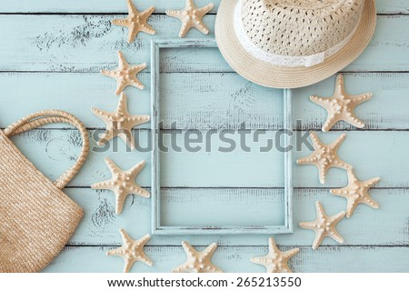 Summer beach decoration: starfishes photo frame with straw hat and handbag on mint wooden background - stock photo