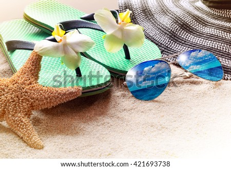 Summer beach. Flip flops and sunglasses on the sand. - stock photo
