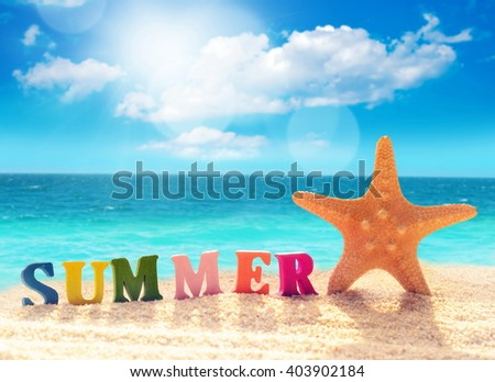 summer beach letters and starfish on a beach sand against the background of the ocean