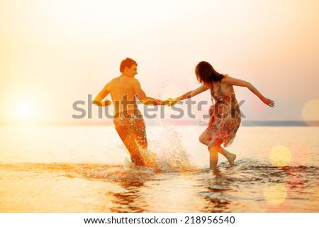 Summer beach party fun holiday on beach background. Couple in love in beach party. Summer scene about sunset sky. - stock photo