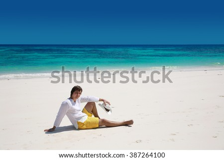 Summer beach. Relax. Successful handsome man resting on exotic beach with blue water and white sand. Vacation Travel. Bliss freedom seashore concept.  - stock photo