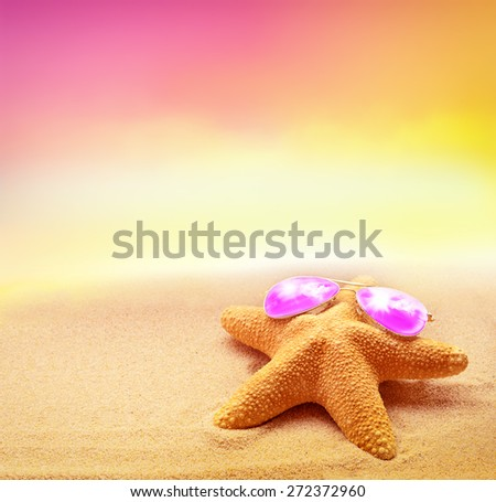 Summer beach. Starfish in pink sunglasses on the seashore. - stock photo