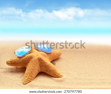 Summer beach. Starfish in sunglasses on the seashore. - stock photo