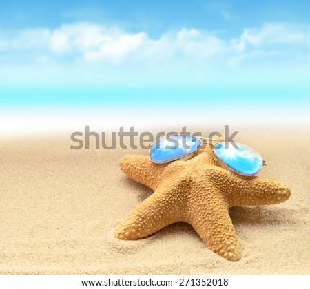 Summer beach. Starfish in sunglasses on the seashore. - stock photo