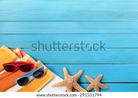 Summer beach sunbathing border, blue wood background, copy space - stock photo