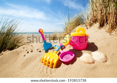 Summer beach toys in the sand concept for holiday and vacations - stock photo
