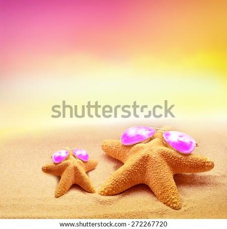 Summer beach. Two Starfish in pink sunglasses on the seashore. - stock photo