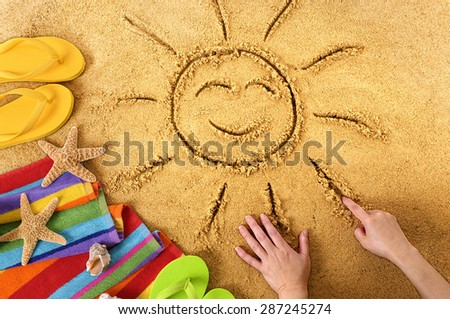 Summer beach vacation, child drawing smiling face sun - stock photo