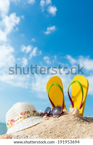 Summer beach vacation concept with flip flop, sunglasses and floppy hat - stock photo