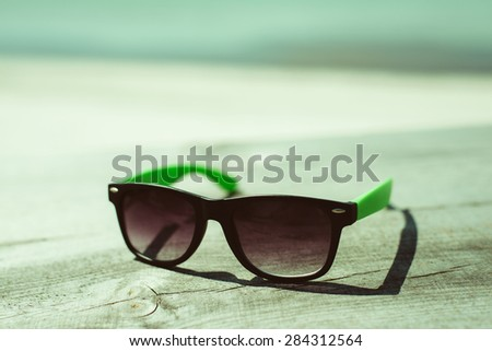Summer beach vacation in the sun, sun glasses on a table near the ocean.  - stock photo