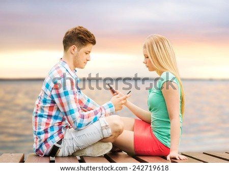 summer beach, vacation, technology, addiction and friendship concept - couple with smartphones sitting on bench over sunset at sea side - stock photo
