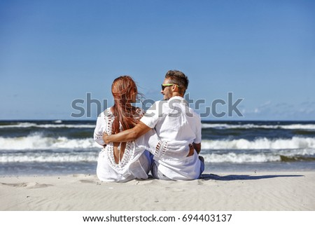 summer beach with ocean and two lovers
