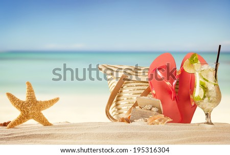 Summer beach with red sandals, drink and accessories - stock photo