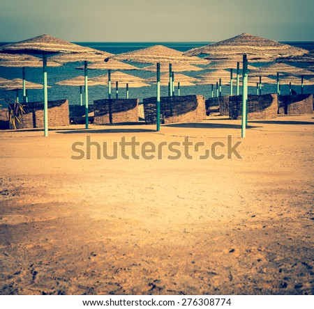 Summer beach with sun umbrellas in retro style. Beach chair on a tropical sand beach. Resort vacation on the beach of summertime. Vintage Instagram style filter effect. Copy-spase for your text. - stock photo