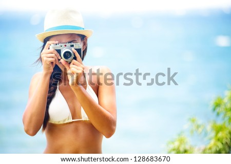 Summer beach woman holding vintage retro camera taking pictures looking at camera during summer holiday vacation travel at the ocean. - stock photo
