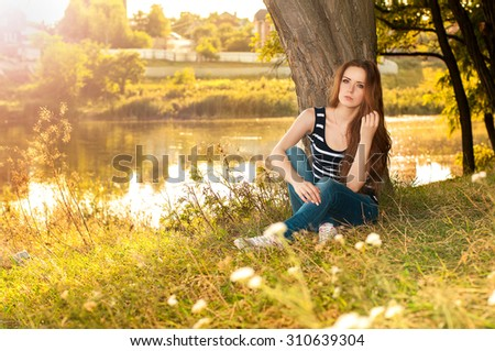 Summer beauty girl. Beautiful young woman lying on green grass outdoor. Park. Meadow. Spring girl lying on the field. Happiness. Outdoors.  - stock photo