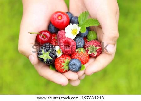 Summer berry fruits in handsgreen grass background. - stock photo