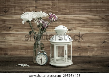summer bouquet of flowers and vintage lantern with old alarm clock on the wooden background - stock photo