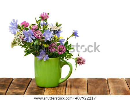 Summer bouquet of Meadow flowers in a cup on a wooden background.