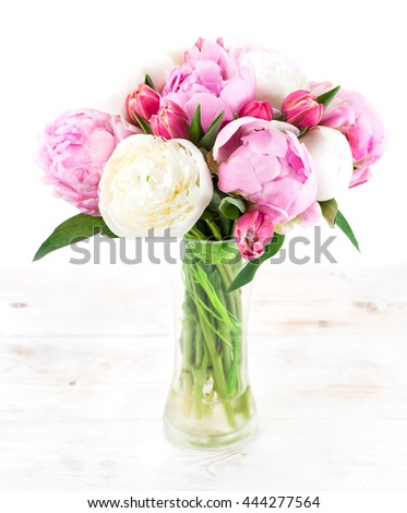 Summer bouquet of peonies in a glass vase on a white wooden table - stock photo