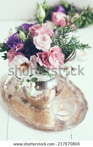 Summer bouquet of purple and pink eustomas in an antique coffee pot on a white wooden board, vintage style, holiday and wedding elegant floral decor