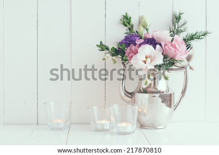 Summer bouquet of purple and pink eustomas in an antique coffee pot on a white wooden board, vintage style, holiday and wedding floral background, pastel colors - stock photo