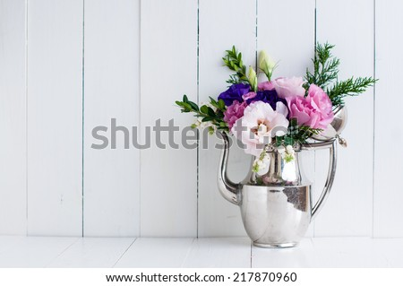 Summer bouquet of purple and pink eustomas in an antique coffee pot on a white wooden board, vintage style, holiday and wedding floral background - stock photo