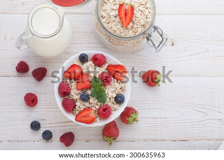 Summer breakfast. Ingredients for healthy breakfast - berries, fruit and muesli on white wooden table, close-up top view horizontal.