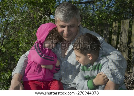 Summer bright sunny day in the village on the street hugging grandchildren grandfather boy and a girl. - stock photo