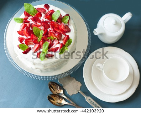 Summer cake with strawberries and mint decorated with whipped cream on stand with tea accessories, close up, top view - stock photo