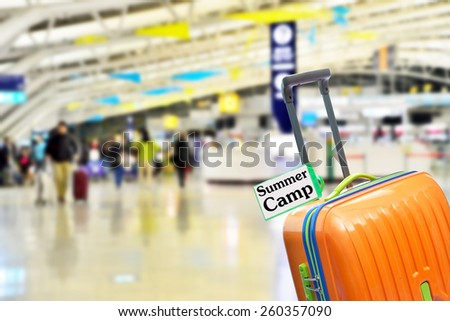 Summer Camp. Orange suitcase with label at airport. - stock photo