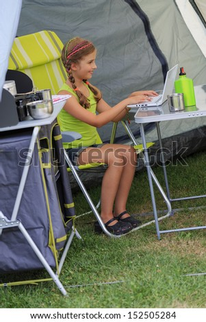 Summer camp - young girl playing in the tent - stock photo