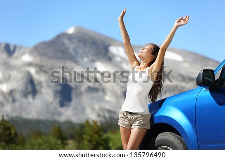 Summer car travel freedom woman in Yosemite National Park with arms raised up cheerful and happy. Summer road trip traveler concept from Yosemite National Park, California, USA. - stock photo