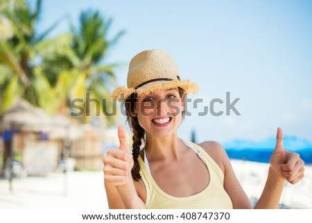 Summer caribbean vacation travel. Successful happy woman doing thumbs up approving gesture at tropical beach. Playa del Carmen, Mexico. - stock photo