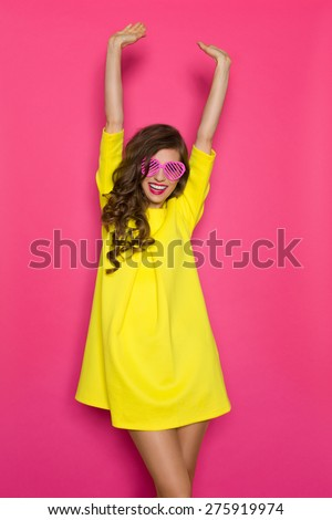 Summer Celebration. Beautiful girl in yellow mini dress and pink heart shaped sunglasses posing with arms raised. Three quarter length studio shot on pink background. - stock photo