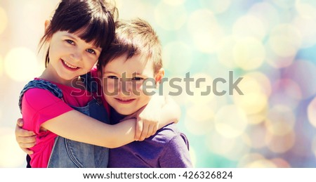 summer, childhood, family, friendship and people concept - two happy kids hugging over blue lights background - stock photo