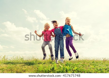 summer, childhood, leisure and people concept - group of happy kids jumping high on green field outdoors - stock photo