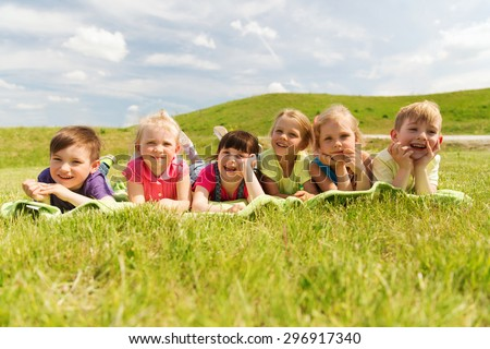 summer, childhood, leisure and people concept - group of happy kids lying on blanket or cover outdoors - stock photo
