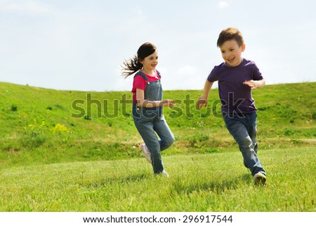 summer, childhood, leisure and people concept - happy little boy and girl playing tag game and running outdoors on green field - stock photo