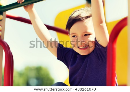 summer, childhood, leisure and people concept - happy little boy on children playground climbing frame