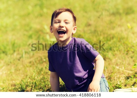 summer, childhood, leisure and people concept - happy little boy sitting on grass and laughing outdoors - stock photo