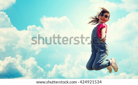 summer, childhood, leisure and people concept - happy little girl jumping high over blue sky and clouds background - stock photo
