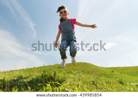 summer, childhood, leisure and people concept - happy little girl jumping high over green field and blue sky outdoors