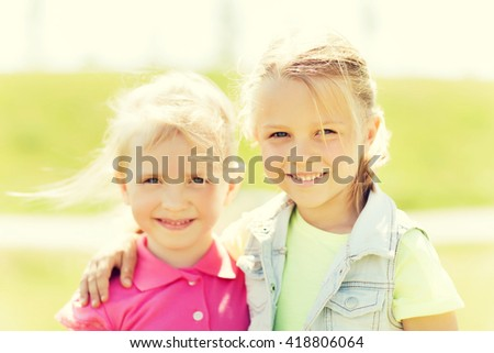 summer, childhood, leisure and people concept - happy little girls hugging outdoor - stock photo