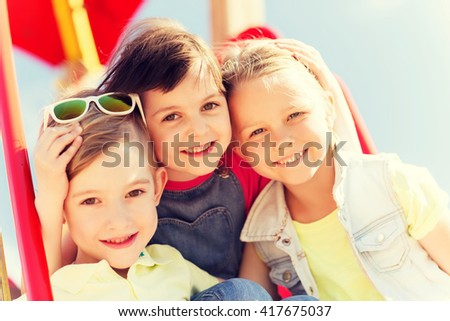 summer, childhood, leisure, friendship and people concept - group of happy kids hugging on children playground